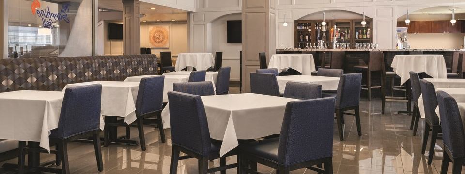 On-site restaurant featuring a bar, dark blue chairs and tables with white tablecloths