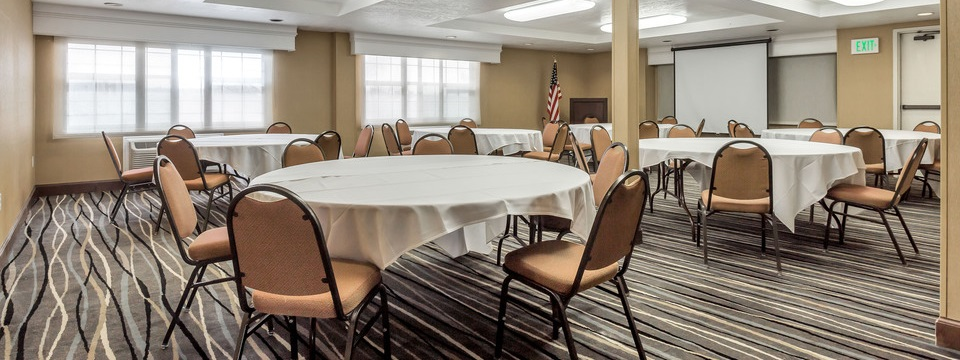 Round tables with white tablecloths in an elegant banquet space