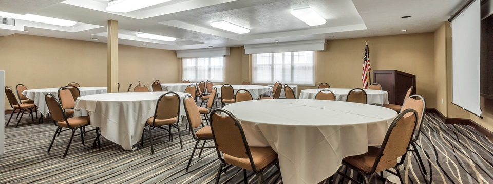 Meeting room with round tables, a podium and a projection screen