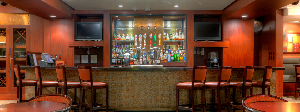 Well-stocked hotel bar with eight stools