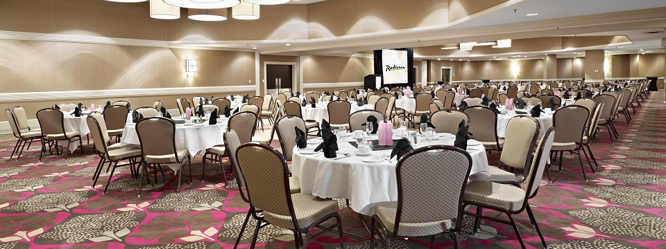 Ballroom with dozens of tables and a projector screen
