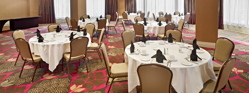 Six round tables in modern hotel ballroom