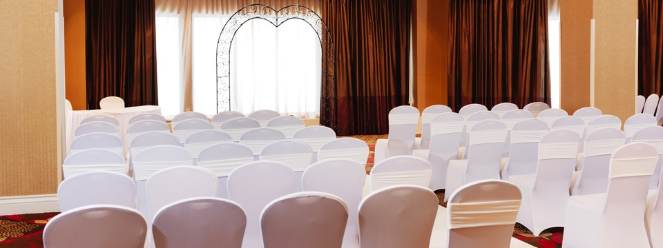 Event space set up for a wedding, including white chairs and an archway