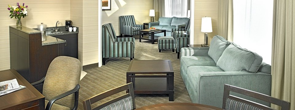 Suite with comfortable sitting areas, a wet bar, a work desk and natural light