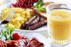 Breakfast platter with eggs, sausage, toast and orange juice