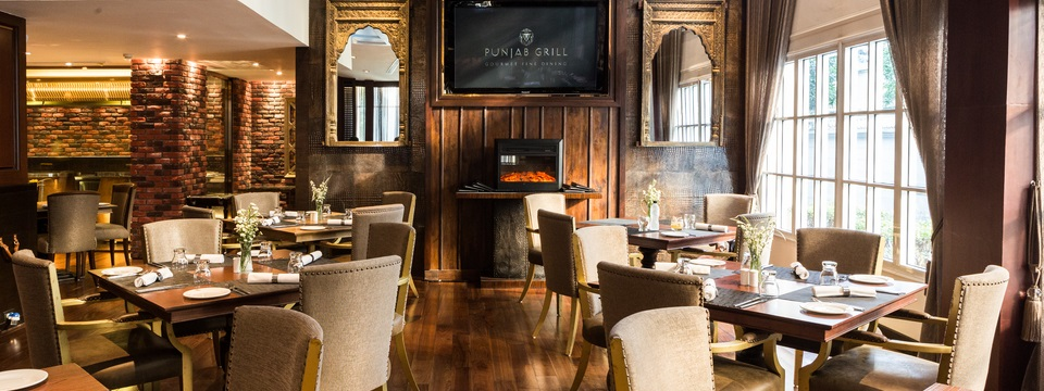 Punjab Grill featuring brick accent walls and warm wood tones