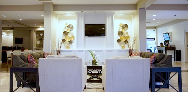 Modern hotel lobby with brown couches, white armchairs and a flat-screen TV
