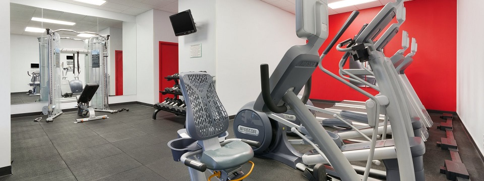 Hotel fitness center with Precor equipment and a red accent wall