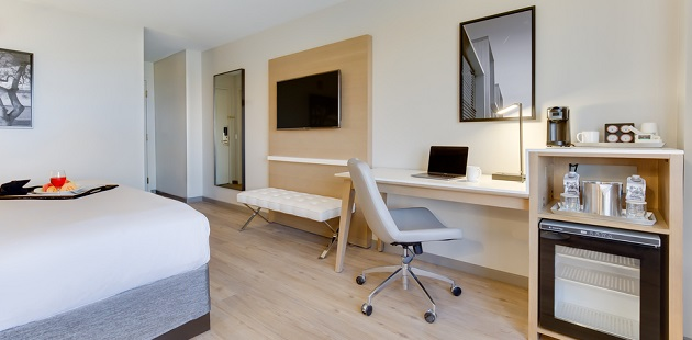 Guest room with a mini fridge, work desk, flat-screen TV and full-length mirror