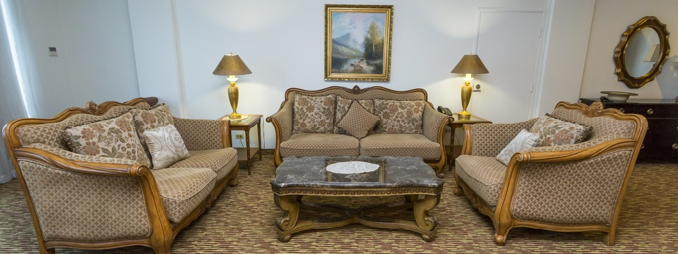 Suite's living room with three loveseats and a coffee table