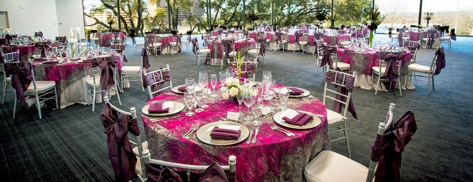 Tables and chairs covered in purple linens in event space