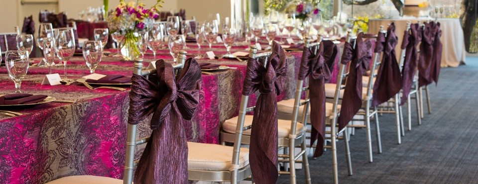 Banquet table with purple linens and place settings
