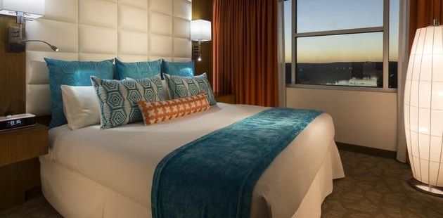 Hotel suite featuring a king bed with patterned, teal pillows and a view of the city