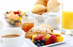 Table set with fruit, pastries, juice and coffee
