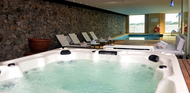 Bubbling hot tub and indoor pool by stone wall