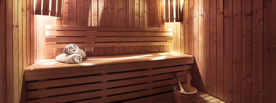 Towels sitting on wooden bench in hotel's dry sauna