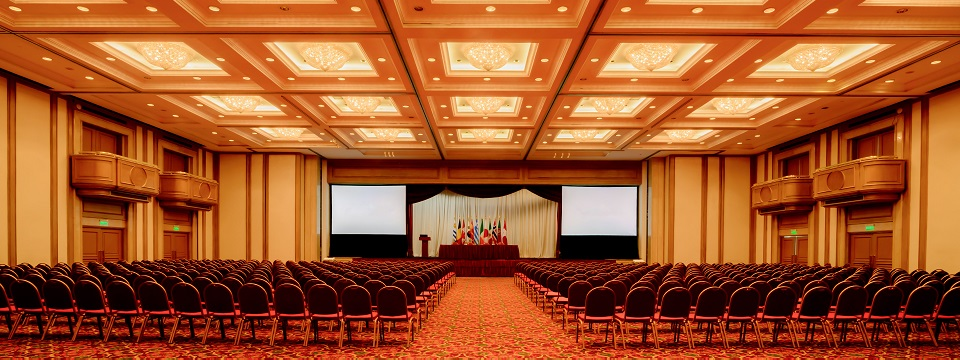 Elegant ballroom with rows of chairs and balconies overlooking stage