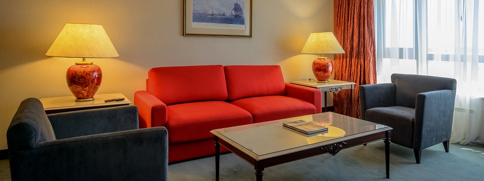 Living area with red couch, armchairs and coffee table