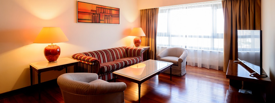 Spacious suite with hardwood floors, patterned sofa and armchairs