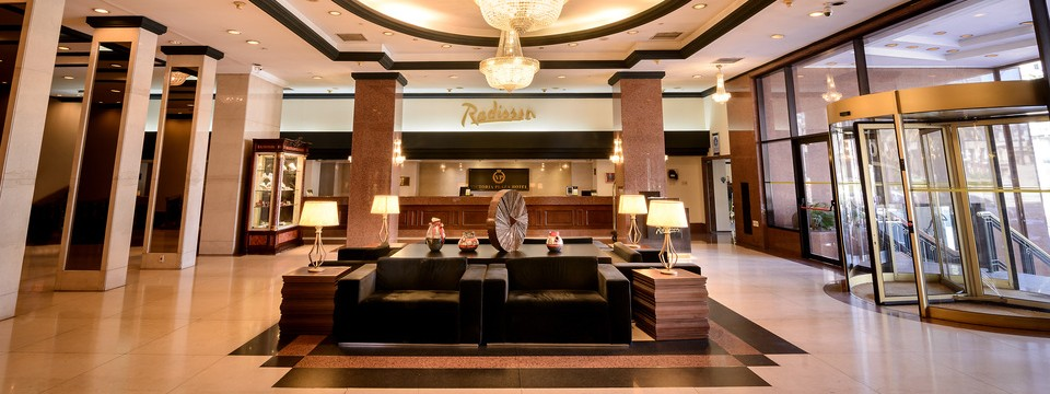 Spacious hotel lobby with gold Radisson sign