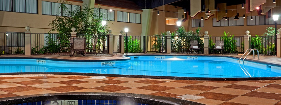 Albany hotel with indoor pool surrounded by chairs and plants