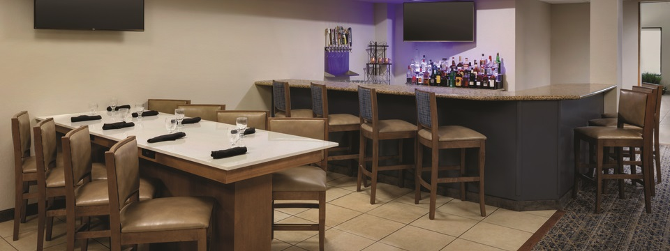 Bar area featuring a party table and two flat-screen TVs