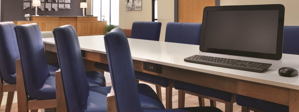 Business center with a desktop computer and several blue leather chairs