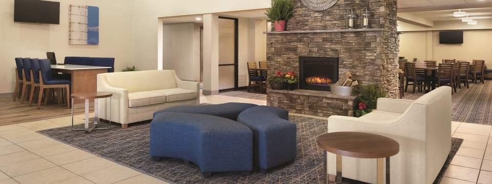 Hotel lobby with sofas, a fireplace, a dining room and a business center