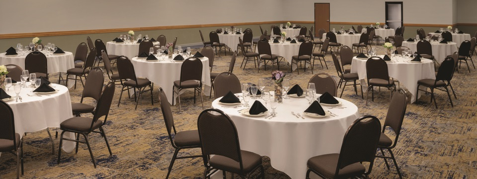 Hotel meeting space with tables and chairs arranged for a banquet