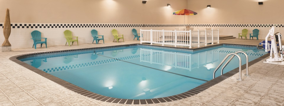 Indoor pool area with blue and green patio chairs set against the the wall