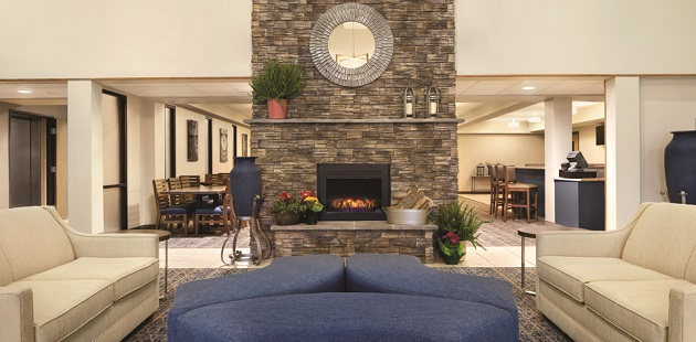 Hotel lobby with tan sofas and blue ottomans arranged in front of a fireplace