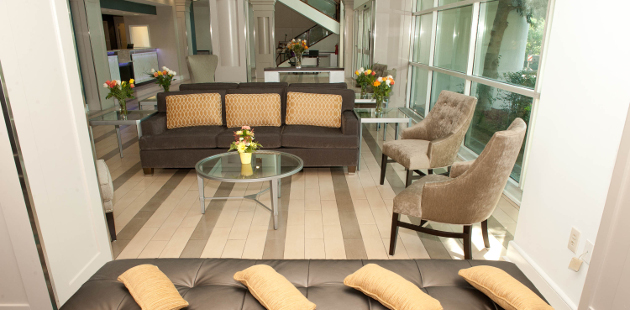 Spacious hotel lobby with couch, chairs and flower arrangements