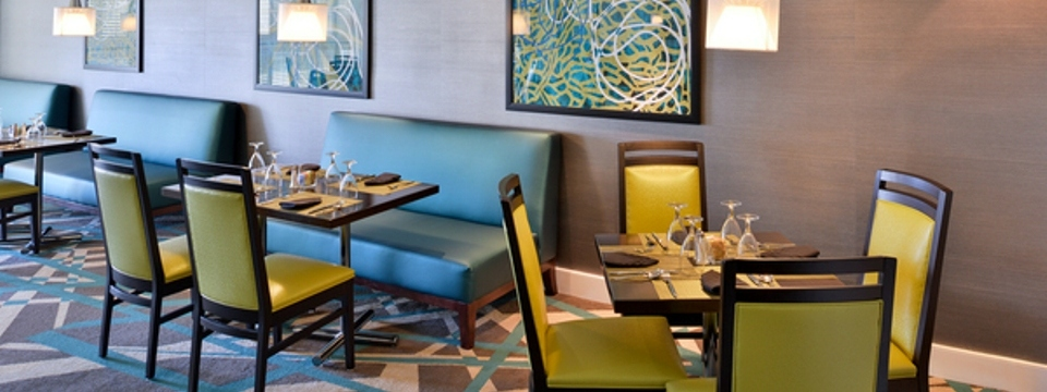 Yellow chairs and teal booths in dining area
