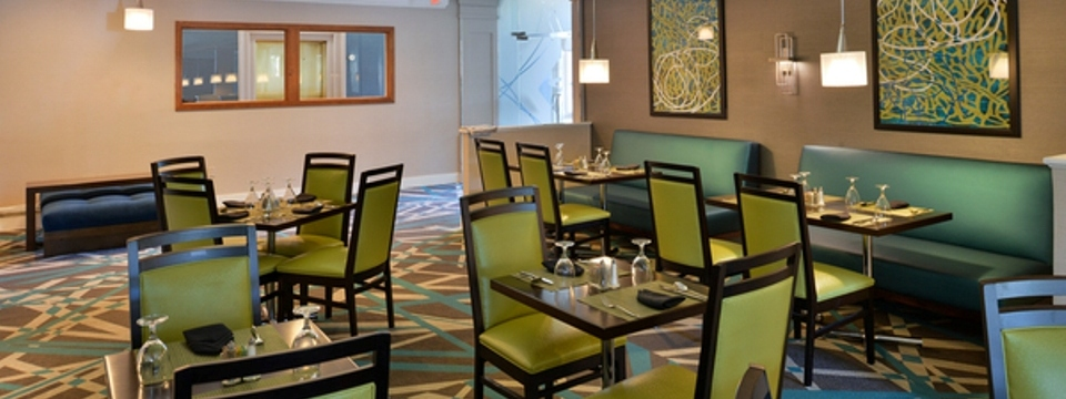 Eclectic dining area with tables, chairs, booths and abstract wall art