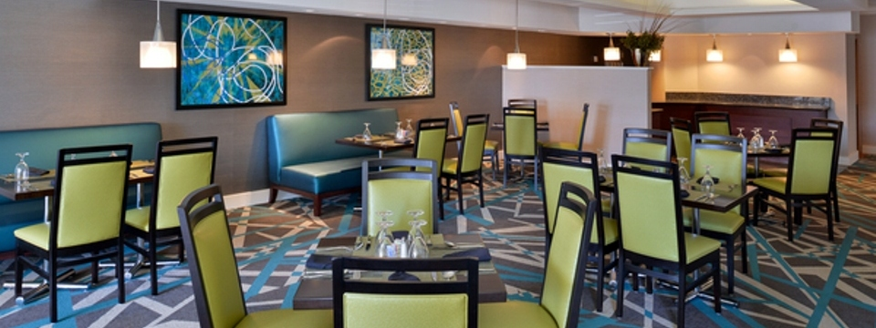 Yellow and teal dining area with tables, chairs and patterned carpet