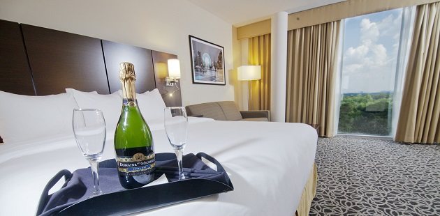 Hotel room with champagne and glasses on bed