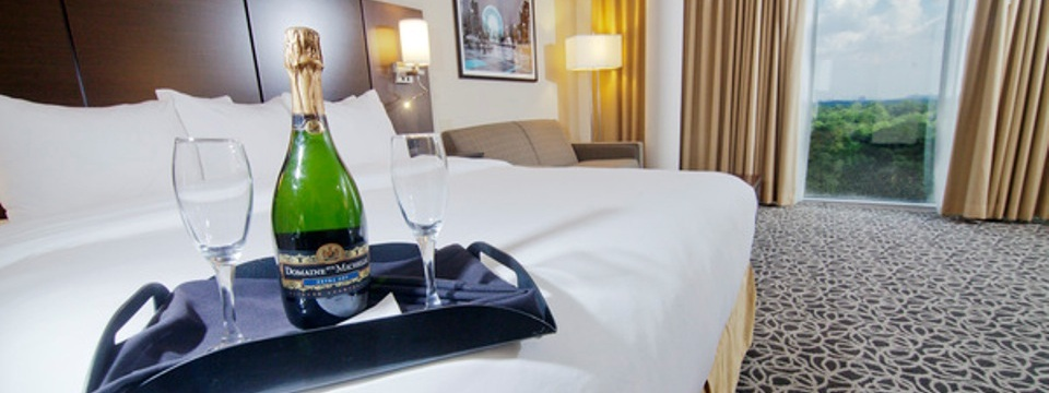 Champagne and drink glasses on plush hotel bed