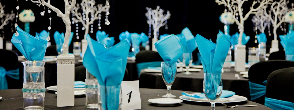 Crystal-studded table accents with teal napkins and ribbons