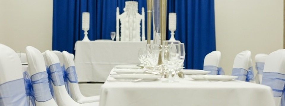 White tables and chairs wrapped in blue ribbon in elegant event space