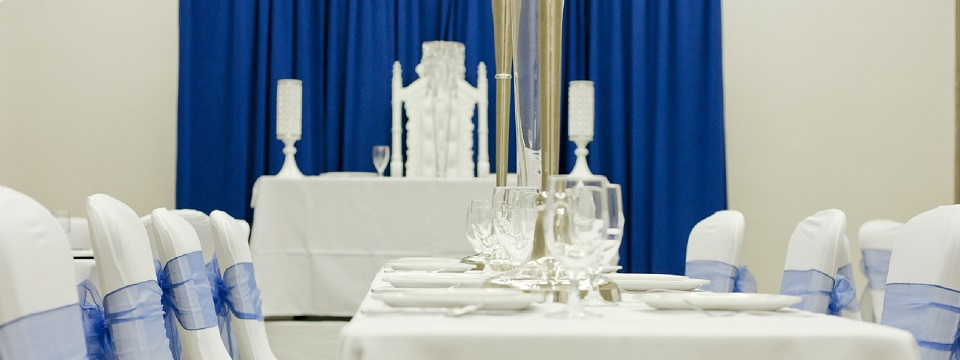 Banquet setting with white linen, cutlery and blue ribbon accents