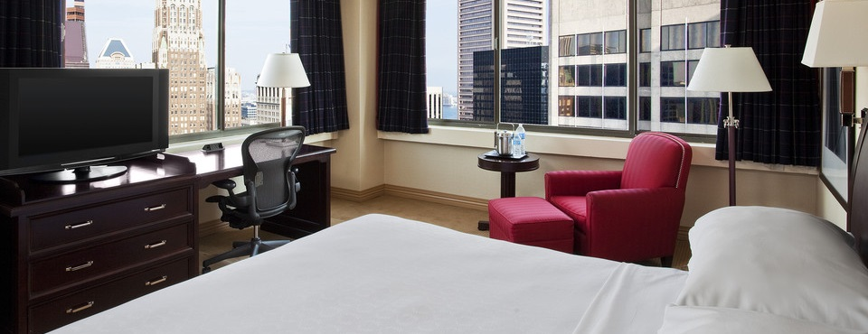 Guest room with city views, flat-screen TV and red armchair