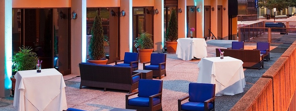 Outdoor sitting area with blue chairs and sofas at dusk