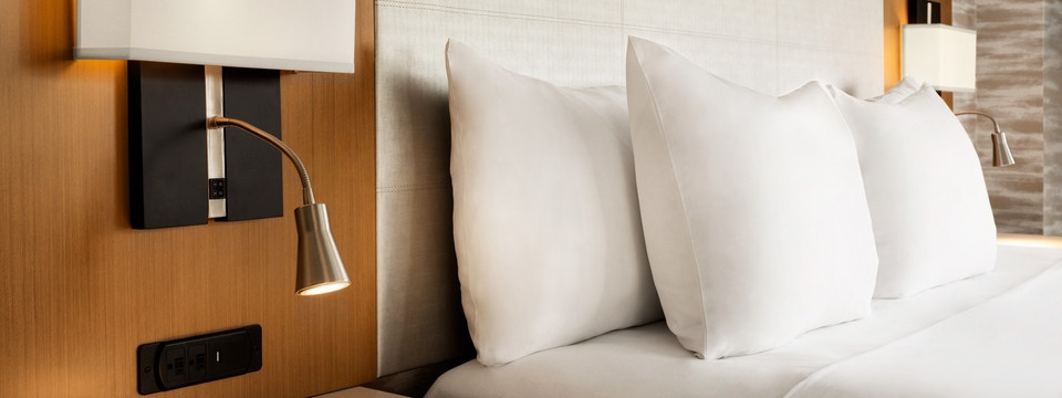 Guest bed with crisp, white linens and comfortable pillows