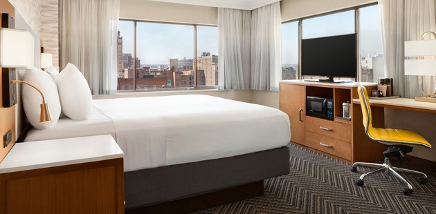 Corner room featuring a comfortable bed, a flat-screen TV and views of the city