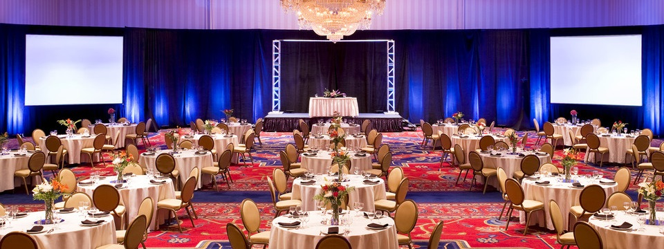 Large ballroom with elegant chandelier and round tables with floral arrangements