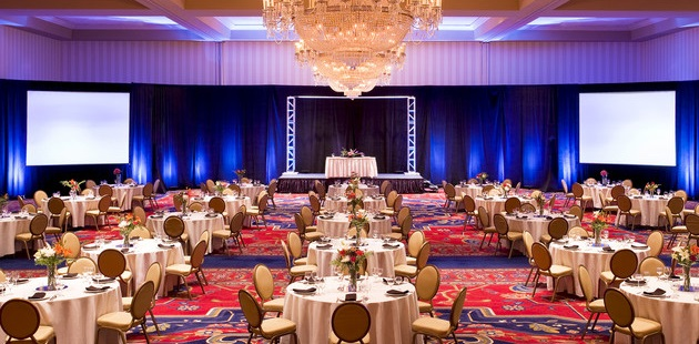 Spacious ballroom with elegant chandelier, round tables and chairs