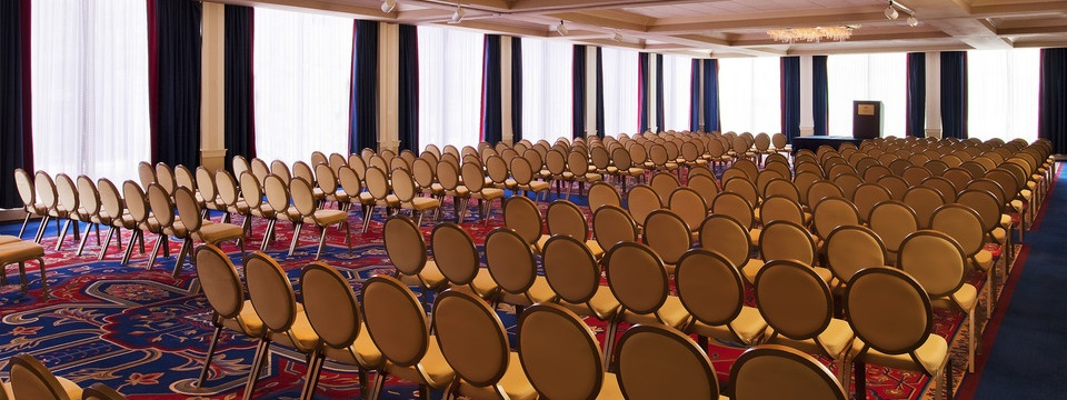Rows of chairs facing podium in event space