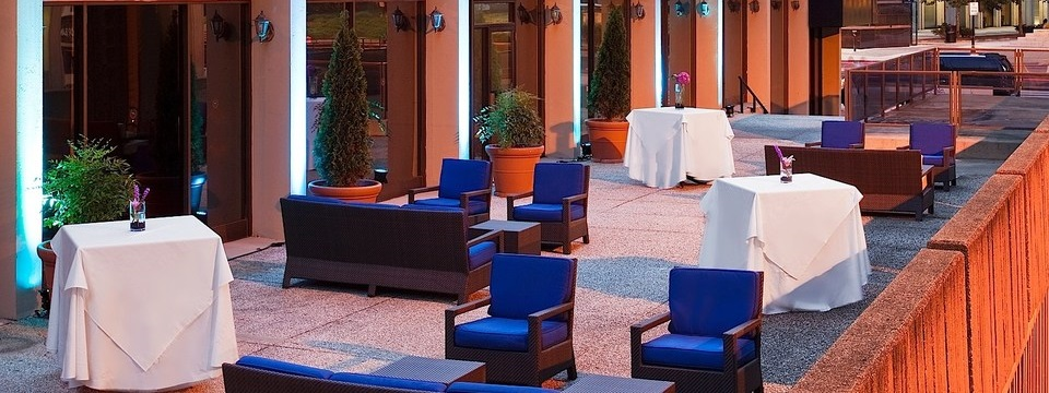 Outdoor venue with blue couches, chairs and white high tops