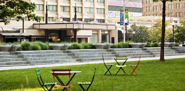 Green space with tables and chairs in front of hotel exterior
