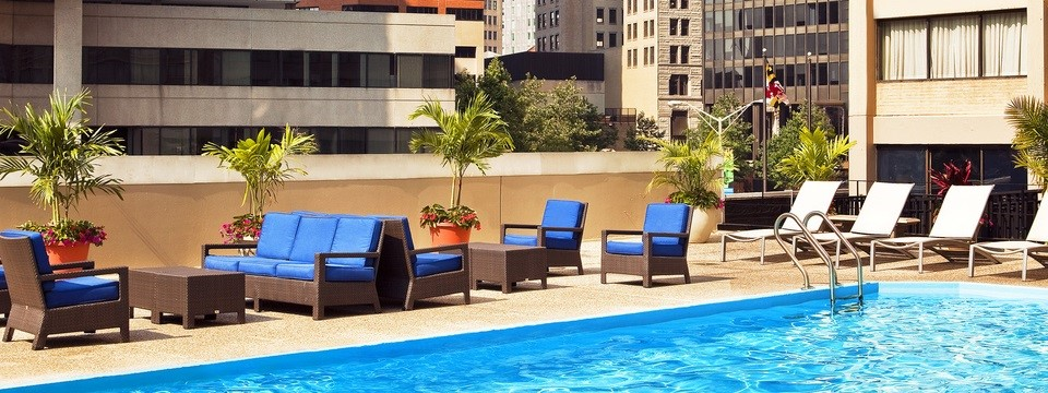 Outdoor rooftop pool surrounded by blue seating and lounge chairs